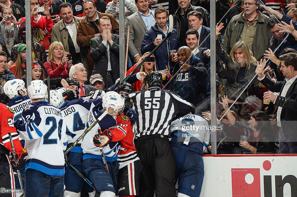 Linesman Shane Heyer #55 attempts to break up the fight between the Jets and the Blackhawks after the glass gave way from a hard check to <a gi-track='captionPersonalityLinkClicked' href=/galleries/search?phrase=Adam+Pardy&family=editorial&specificpeople=2221762 ng-click='$event.stopPropagation()'>Adam Pardy</a> #2 of the Winnipeg Jets from Brandon Bollig #52 of the Chicago Blackhawks during the NHL game on November 06, 2013 at the United Center in Chicago, Illinois.