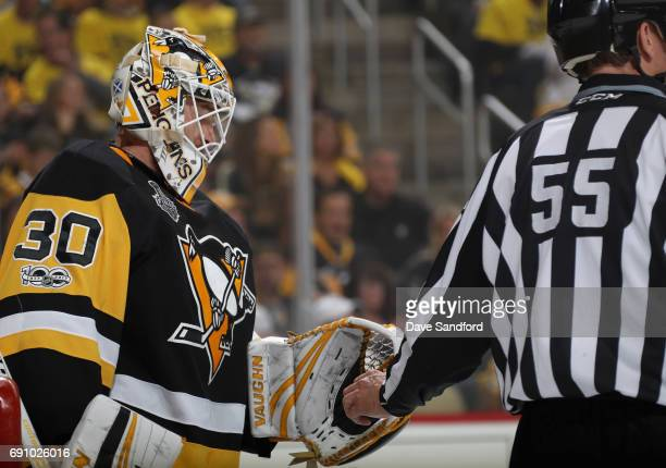 Linesman Shane Heyer takes the puck from goaltender Matt Murray of the Pittsburgh Penguins during the first period of Game Two of the 2017 NHL...