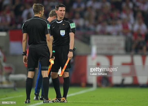 Linesman Stefan Lupp stands with Mark Borsch while they wait for the 4th official to come on as new referee during the Bundesliga match between 1 FC...