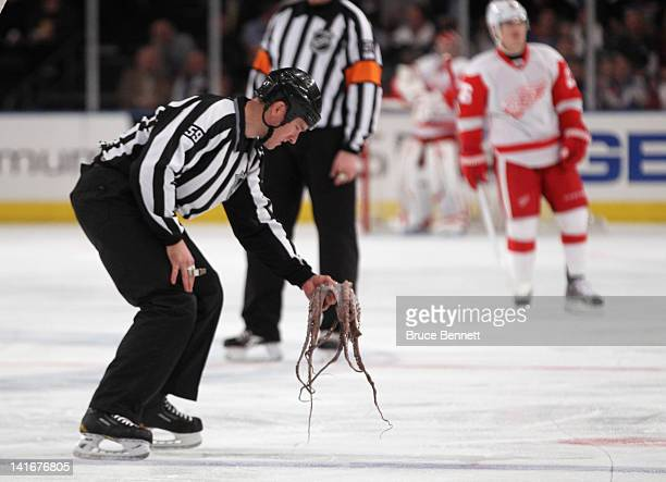 Linesman Steve Barton removes an octopus from the ice following a first period goal by Henrik Zetterberg of the Detroit Red Wings against the New...