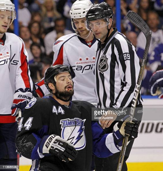 Linesman Steve Miller checks on Nate Thompson of the Tampa Bay Lightning after running into goaltender Michal Neuvirth of the Washington Capitals in...