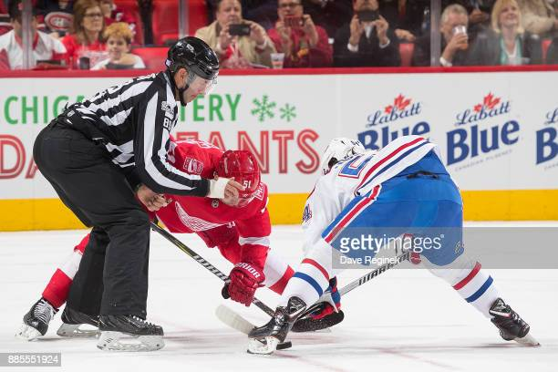 Linesman Steve Miller drops the puck between Frans Nielsen of the Detroit Red Wings and Charles Hudon of the Montreal Canadiens during an NHL game at...