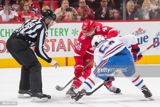 Linesman Steve Miller drops the puck between Luke Glendening of the Detroit Red Wings and Charles Hudon of the Montreal Canadiens during an NHL game...