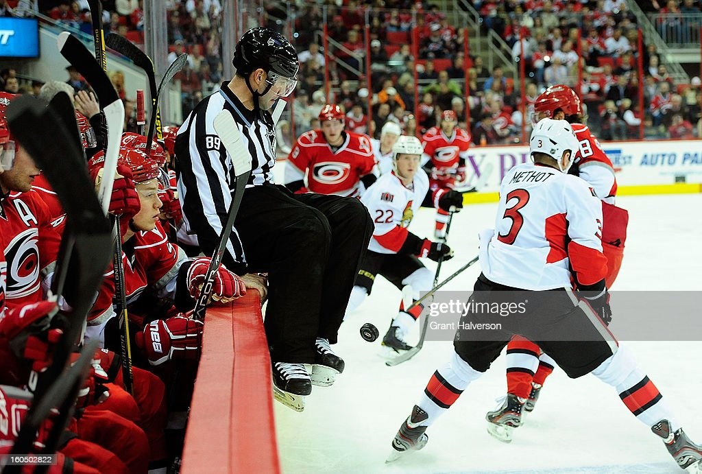 NHL linesman Steve Miller #89 leaps to avoid being hit by the puck during a game between the Ottowa Senators and the Carolina Hurricanes during play at PNC Arena on February 1, 2013 in Raleigh, North Carolina.