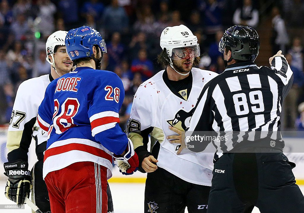 Linesman Steve Miller separates Kris Letang of the Pittsburgh Penguins and Dominic Moore of the New York Rangers after a fight at the end of their 3...