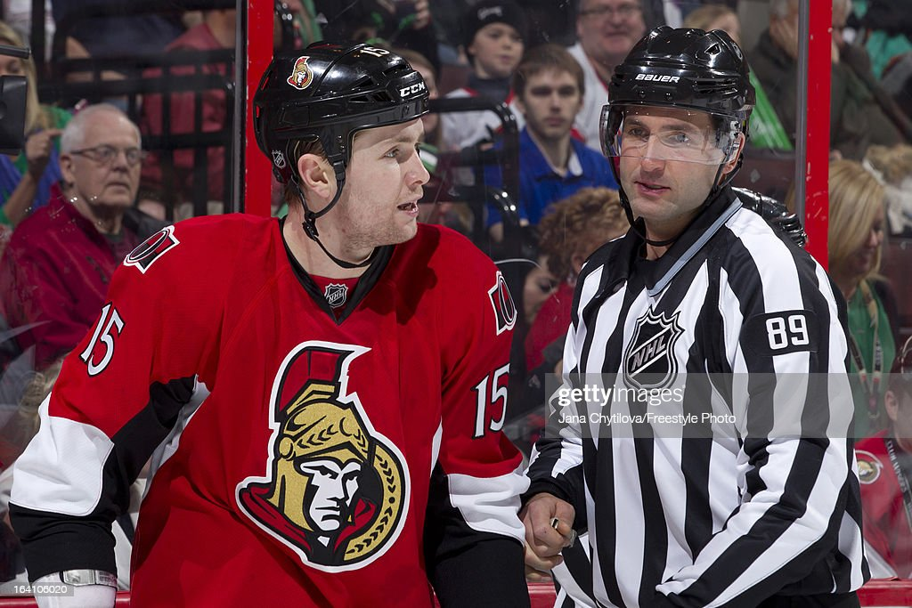 Linesman Steve Miller #89 stands near Zack Smith #15 of the Ottawa Senators after a fight during an NHL game against the Winnipeg Jets at Scotiabank Place on March 17, 2013 in Ottawa, Ontario, Canada.