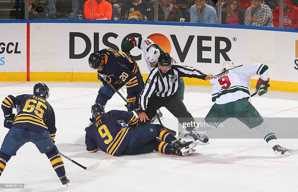 Linesman Steve Miller #89 tries to keep Steve Ott #9 of the Buffalo Sabres and <a gi-track='captionPersonalityLinkClicked' href=/galleries/search?phrase=Mikko+Koivu&family=editorial&specificpeople=584987 ng-click='$event.stopPropagation()'>Mikko Koivu</a> #9 of the Minnesota Wild separated after a faceoff at First Niagara Center on October 14, 2013 in Buffalo, New York. Minnesota won 2-1.