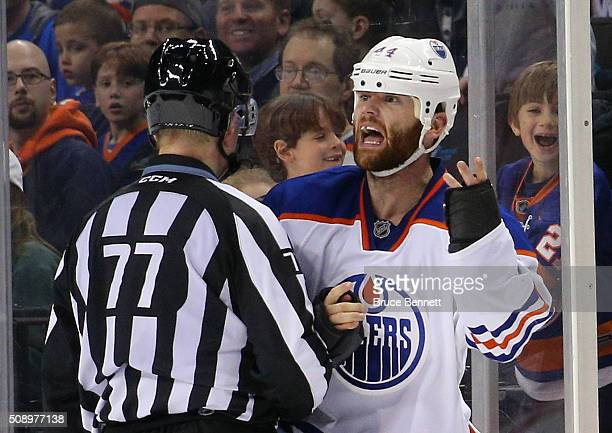 Linesman Tim Nowak escourts Zack Kassian of the Edmonton Oilers off the ice following a fight aganst the New York Islanders at the Barclays Center on...