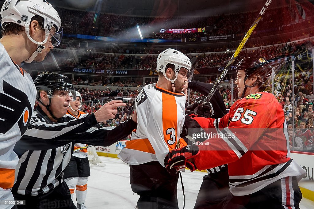 Linesman Tony Sericolo #84 breaks up a scuffle between Radko Gudas #3 of the Philadelphia Flyers and Andrew Shaw #65 of the Chicago Blackhawks in the first period of the NHL game at the United Center on March 16, 2016 in Chicago, Illinois.