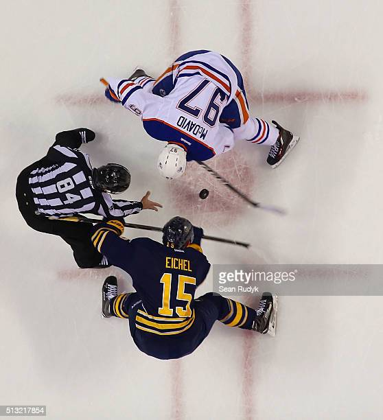 Linesman Tony Sericolo drops the puck during a faceoff between Jack Eichel of the Buffalo Sabres and Connor McDavid of the Edmonton Oilers during an...