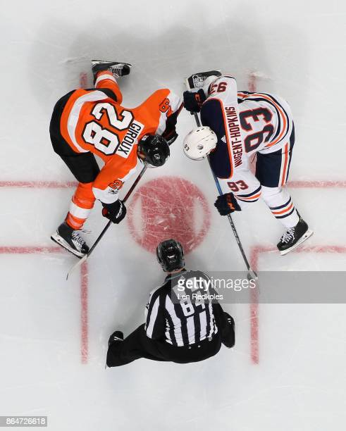 Linesman Tony Sericolo watches as Claude Giroux of the Philadelphia Flyers faces off with Ryan NugentHopkins of the Edmonton Oilers on October 21...