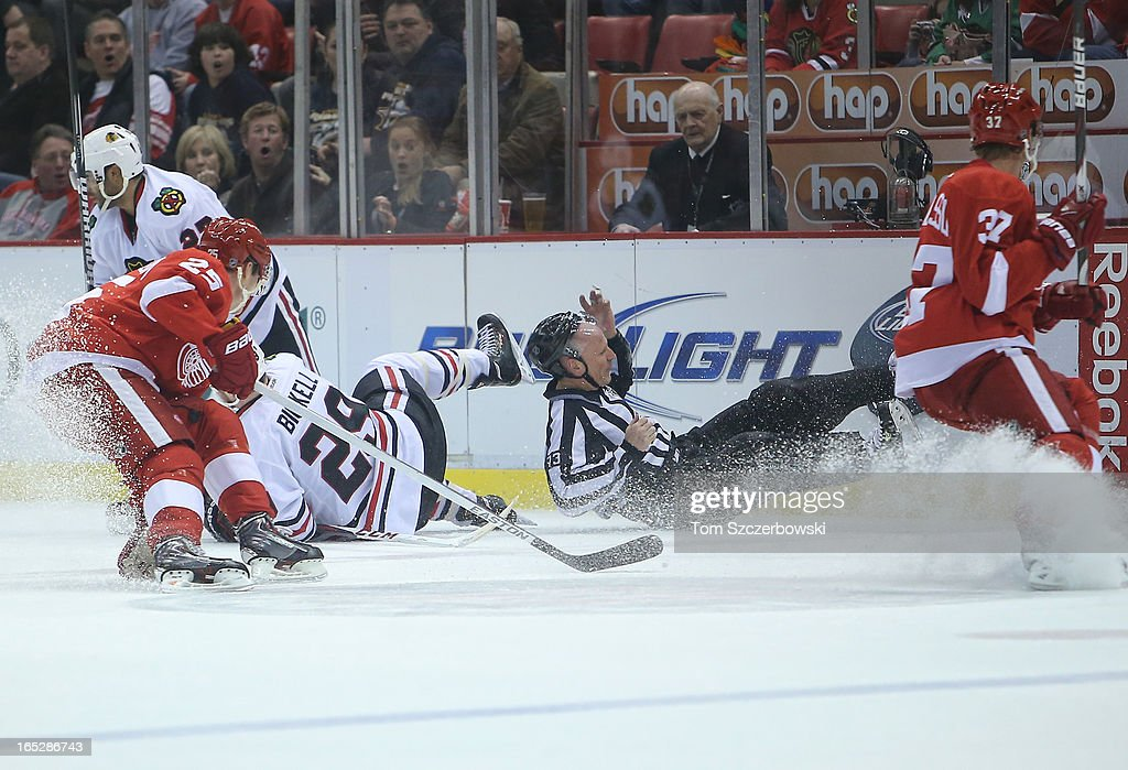 Linesman Vaughan Rody #73 falls during the Chicago Blackhawks NHL game against the Detroit Red Wings at Joe Louis Arena on March 31, 2013 in Detroit, Michigan.