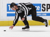 Linesman Vaughan Rody picks up the puck during the NHL game between the Vancouver Canucks and the Minnesota Wild at Rogers Arena January 4 2012 in...