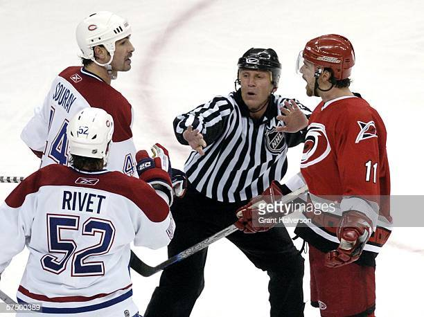 Linesman Vaughan Rody separates Justin Williams of the Carolina Hurricanes from Sheldon Souray and Craig Rivet of the Montreal Canadiens in game five...