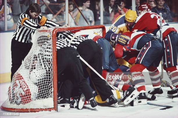 Linesmen and the referee try to break up a fight in the goal mouth net between the players of the Los Angeles Kings and Washington Capitols during...