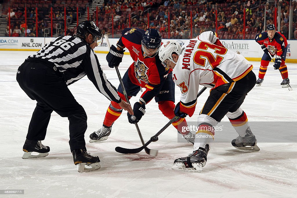 NHL Linesmen Brad Lazarowich #86 drops the puck while Sean Monahan #23 of the Calgary Flames faces off against <a gi-track='captionPersonalityLinkClicked' href=/galleries/search?phrase=Brandon+Pirri&family=editorial&specificpeople=5894589 ng-click='$event.stopPropagation()'>Brandon Pirri</a> #73 of the Florida Panthers at the BB&T Center on April 4, 2014 in Sunrise, Florida.