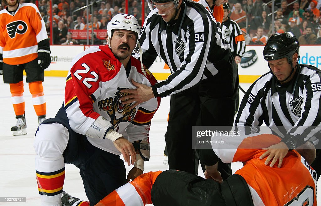Linesmen Bryan Pancich #94 and Jonny Murray #95 separate Nicklas Grossmann #8 of the Philadelphia Flyers from George Parros #22 of the Florida Panthers following their fight in the second period on February 21, 2013 at the Wells Fargo Center in Philadelphia, Pennsylvania.