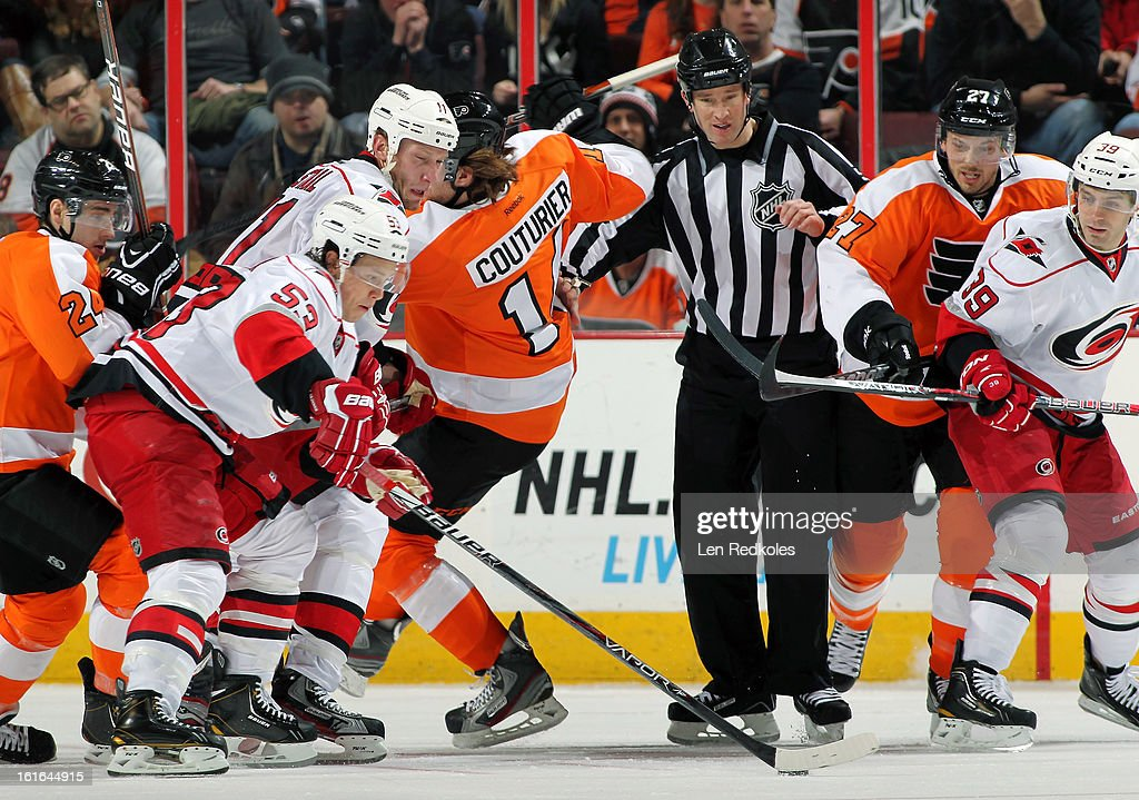 Linesmen Bryan Pancich #94 watches Jeff Skinner #53, Jordan Staal #11 and Patrick Dwyer #39 of the Carolina Hurricanes battle for the puck following a face-off against Sean Couturier #14 and Matt Read #24 of the Philadelphia Flyers on February 9, 2013 at the Wells Fargo Center in Philadelphia, Pennsylvania.