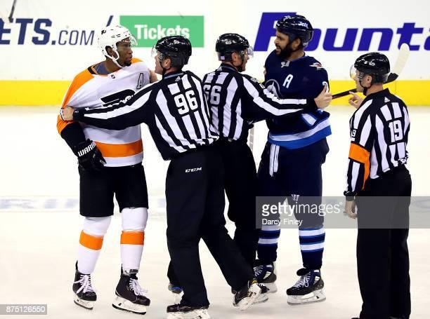 Linesmen David Brisebois and Darren Gibbs hold Wayne Simmonds of the Philadelphia Flyers and Dustin Byfuglien of the Winnipeg Jets apart during a...