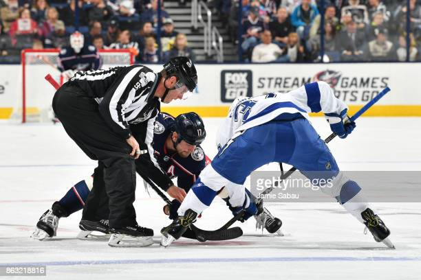 Linesmen David Brisebois drops the puck for a faceoff between Brandon Dubinsky of the Columbus Blue Jackets and Yanni Gourde of the Tampa Bay...