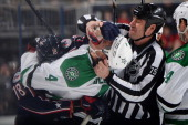 Linesmen Derek Amell tries to break up a scrum between RJ Umberger of the Columbus Blue Jackets and Brenden Dillon of the Dallas Stars during the...