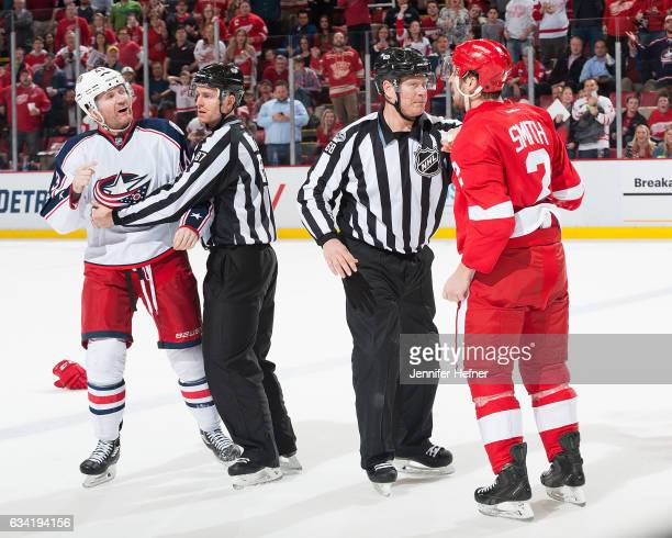 Linesmen Devin Berg and Scott Driscoll break up a fight between Scott Hartnell of the Columbus Blue Jackets and Brendan Smith of the Detroit Red...
