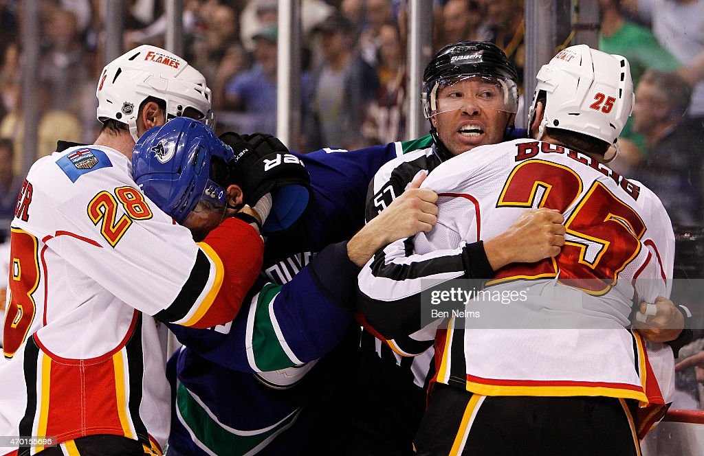 Linesmen Jay Sharrers #57 tries to separate Brandon Bollig #25 of the Calgary Flames and Luca Sbisa #5 of the Vancouver Canucks during Game Two of the Western Conference Quarterfinals during the 2015 NHL Stanley Cup Playoffs at Rogers Arena on April 17, 2015 in Vancouver, B.C, Canada.