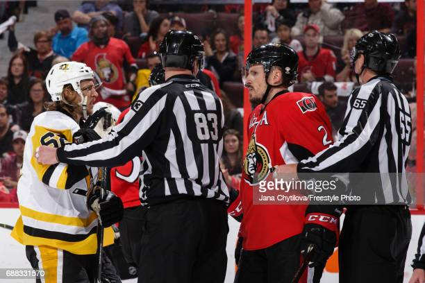 Linesmen Matt MacPherson and Pierre Racicot separate Dion Phaneuf of the Ottawa Senators and Carl Hagelin of the Pittsburgh Penguins in Game Six of...
