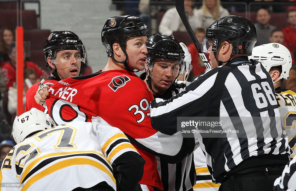 Linesmen Scott Driscoll #68 and Scott Cherrey #50 separate <a gi-track='captionPersonalityLinkClicked' href=/galleries/search?phrase=Matt+Carkner&family=editorial&specificpeople=556901 ng-click='$event.stopPropagation()'>Matt Carkner</a> #39 of the Ottawa Senators from the Boston Bruins players after the whistle during an NHL game at Scotiabank Place on April 5, 2012 in Ottawa, Ontario, Canada.