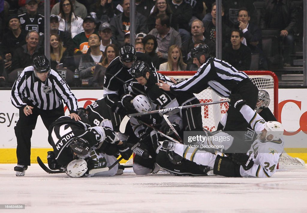 NHL linesmen Shane Heyer #55 and Darren Gibbs #66 break up the scrum in the crease area of goaltender Jonathan Quick #32 of the Los Angeles Kings during the NHL game between the Dallas Stars and the Los Angeles Kings at Staples Center on March 21, 2013 in Los Angeles, California. The Stars defeated the Kings 2-0.