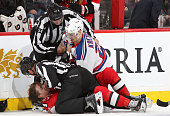 Linesmen Steve Barton and Greg Devorski get between a prone Zack Smith of the Ottawa Senators and Chris Kreider of of the New York Rangers acre a...