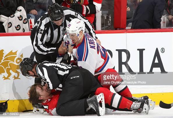 Linesmen Steve Barton and Greg Devorski get between a prone Zack Smith of the Ottawa Senators and Chris Kreider of of the New York Rangers acre a...