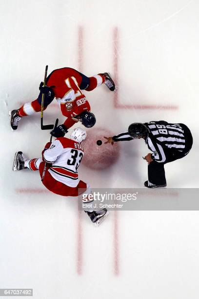 Linesmen Steve Miller drops the puck for a faceoff between Derek MacKenzie of the Florida Panthers and Derek Ryan of the Carolina Hurricanes at the...