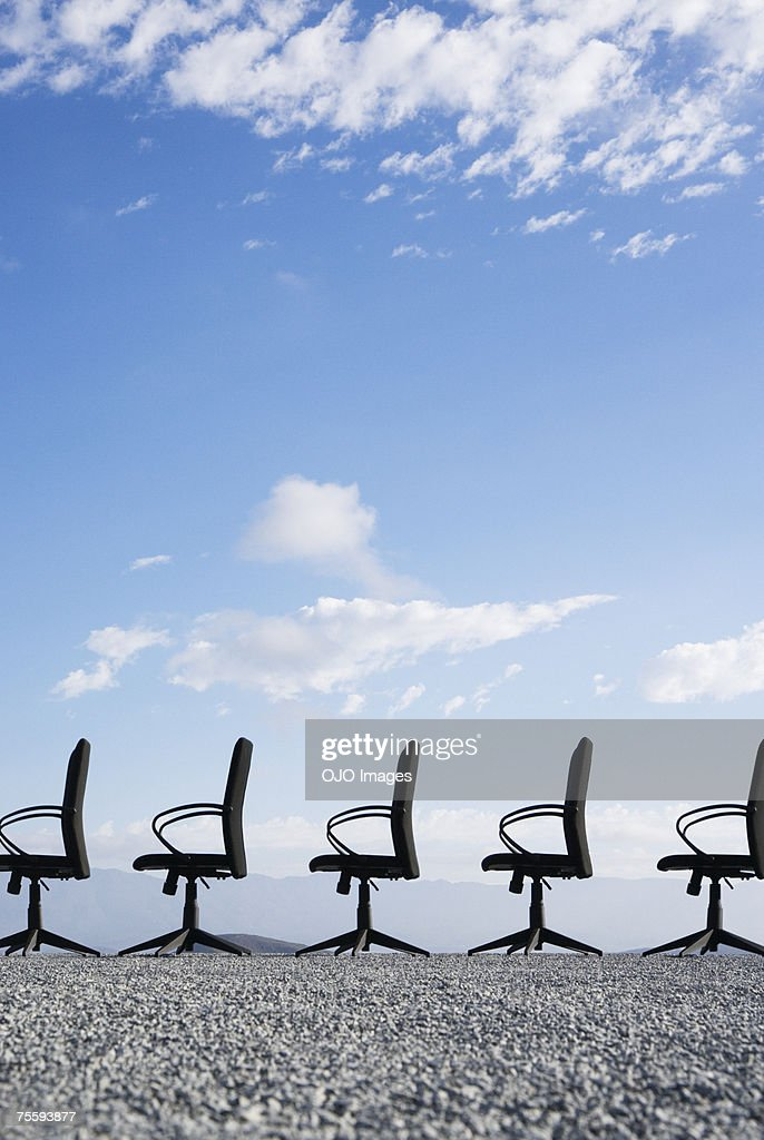 Line-up of empty office chairs in the middle of nowhere : Stock Photo