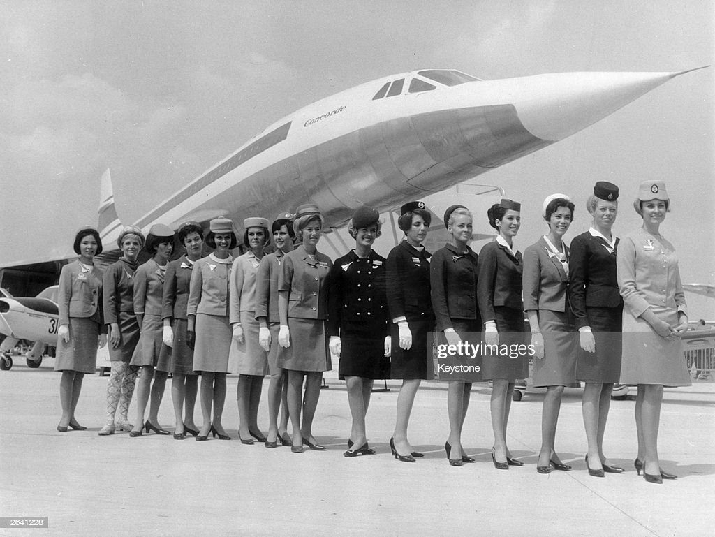 A line-up of some of the air stewardesses who attend to passengers on board the supersonic jet the 'Concorde', each one from a different airline. They are standing in front of a scale model of the aircraft.