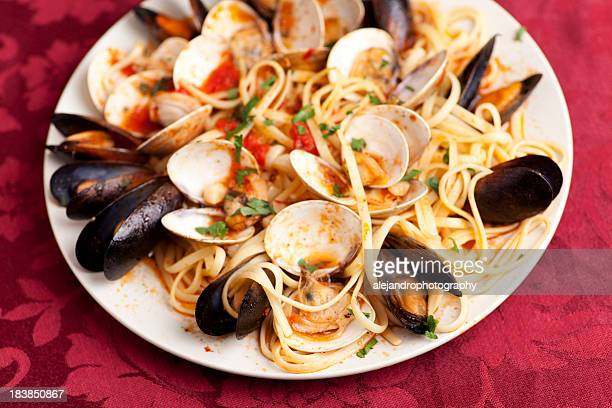 Linguini dish with mussels and clams on red table setting