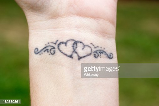 Linked hearts tattoo on wrist