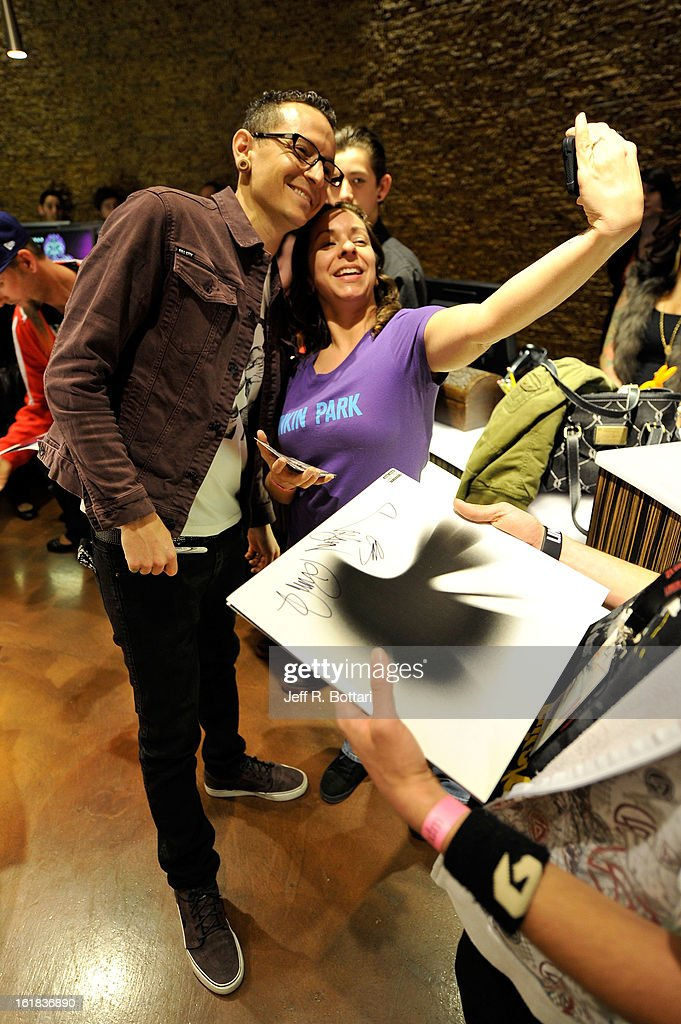 Linkin Park singer <a gi-track='captionPersonalityLinkClicked' href=/galleries/search?phrase=Chester+Bennington&family=editorial&specificpeople=213970 ng-click='$event.stopPropagation()'>Chester Bennington</a> (L) poses with fans during an autograph session at Club Tattoo inside the Miracle Mile Shops at Planet Hollywood Resort & Casino on February 16, 2013 in Las Vegas, Nevada.