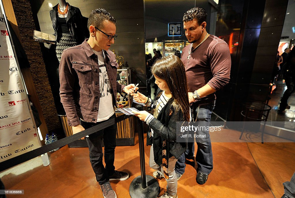 Linkin Park singer Chester Bennington signs an autograph for Isabella Mir, daughter of mixed martial artist Frank Mir, at Club Tattoo inside the Miracle Mile Shops at Planet Hollywood Resort & Casino on February 16, 2013 in Las Vegas, Nevada.