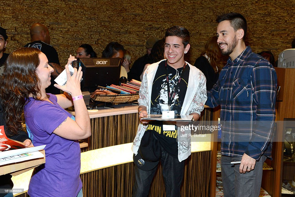 Linkin Park singer/guitarist <a gi-track='captionPersonalityLinkClicked' href=/galleries/search?phrase=Mike+Shinoda&family=editorial&specificpeople=657527 ng-click='$event.stopPropagation()'>Mike Shinoda</a> (R) poses with fans during an autograph session at Club Tattoo inside the Miracle Mile Shops at Planet Hollywood Resort & Casino on February 16, 2013 in Las Vegas, Nevada.