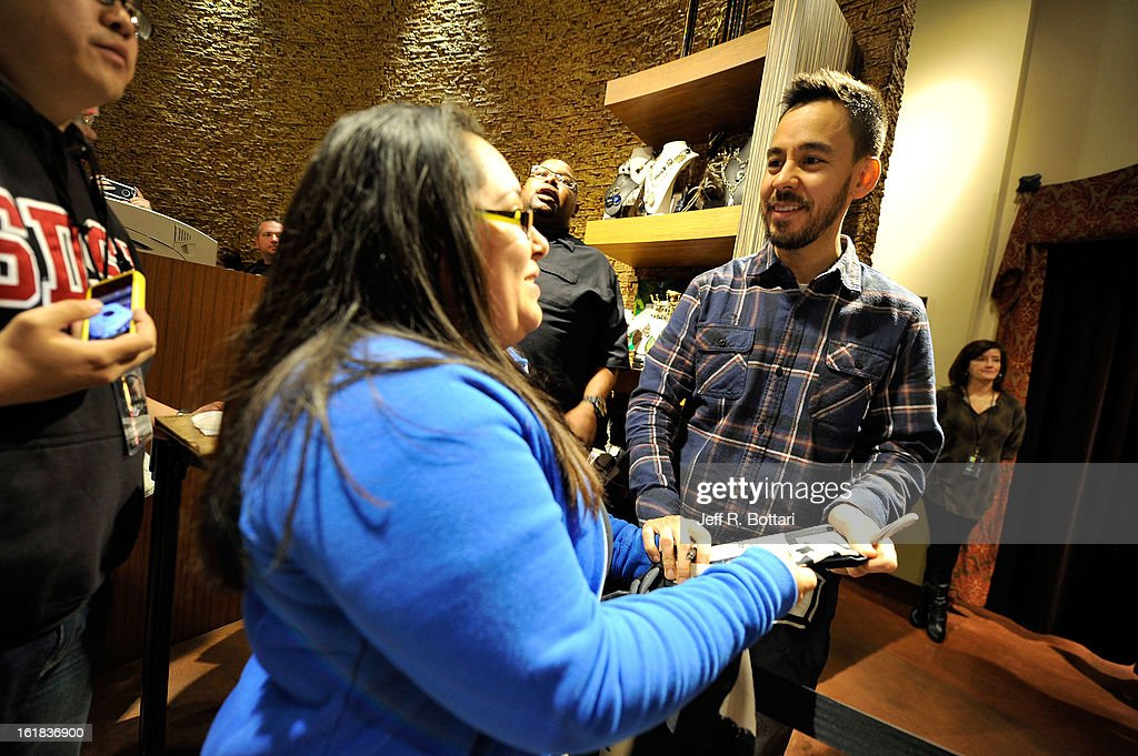 Linkin Park singer/guitarist <a gi-track='captionPersonalityLinkClicked' href=/galleries/search?phrase=Mike+Shinoda&family=editorial&specificpeople=657527 ng-click='$event.stopPropagation()'>Mike Shinoda</a> (R) signs autographs at Club Tattoo inside the Miracle Mile Shops at Planet Hollywood Resort & Casino on February 16, 2013 in Las Vegas, Nevada.
