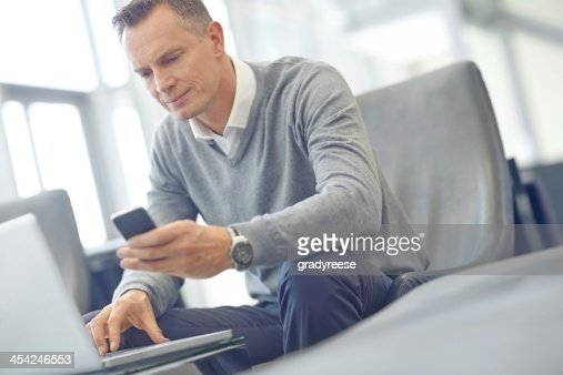 Linking his phone and laptop : Stock Photo
