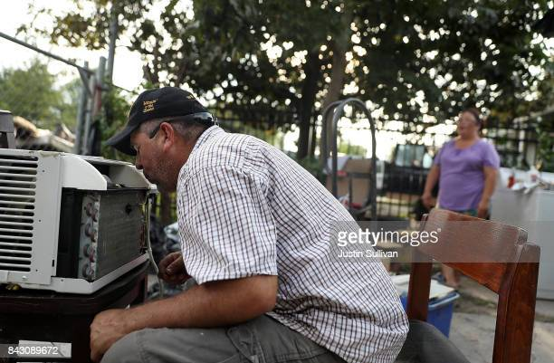Lino Saldana tries to repair a broken air conditioner in front of his flood damaged home on September 5 2017 in Houston Texas Over a week after...