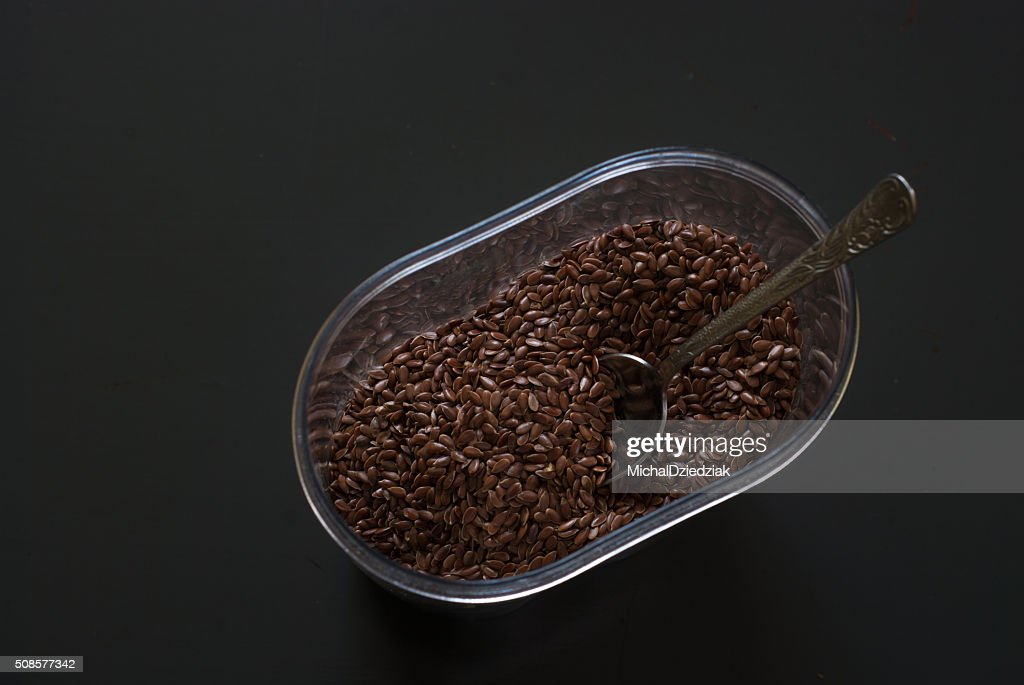 linseed in a plastic box on dark wooden table : Stock Photo
