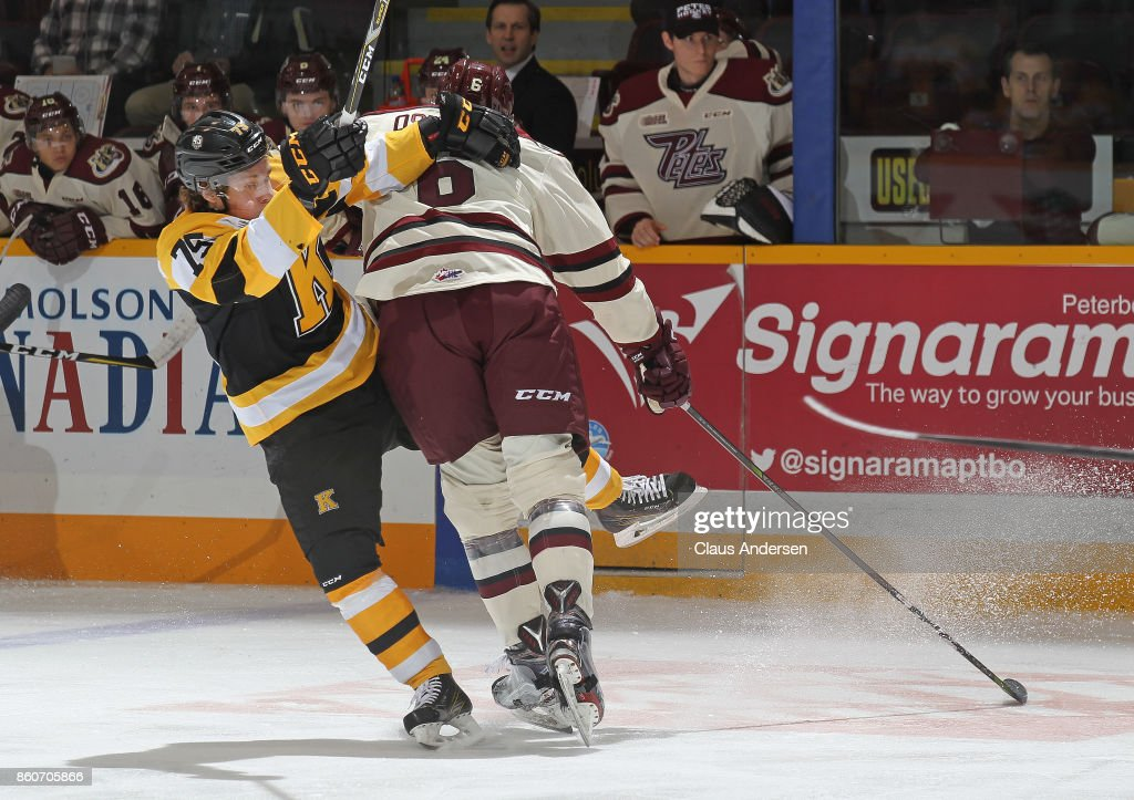 Linus Nyman #75 of the Kingston Frontenacs slams into Auston Osmanski #6 of the Peterborough Petes in an OHL game at the Peterborough Memorial Centre on October 12, 2017 in Peterborough, Ontario.