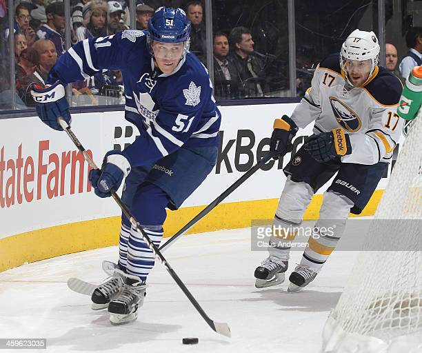 Linus Omark of the Buffalo Sabres skates to check Jake Gardiner of the Toronto Maple Leafs during an NHL game at the Air Canada Centre on December 27...