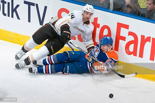 Linus Omark of the Edmonton Oilers takes a hit from Francois Beauchemin of the Anaheim Ducks at Rexall Place on February 13 2011 in Edmonton Alberta...