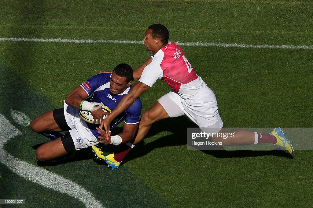 Lio Lolo of Samoa scores a try in the tackle of Dan Norton of England in the semifinal cup match between England and Samoa during the 2013 Wellington Sevens at Westpac Stadium on February 2, 2013 in Wellington, New Zealand.