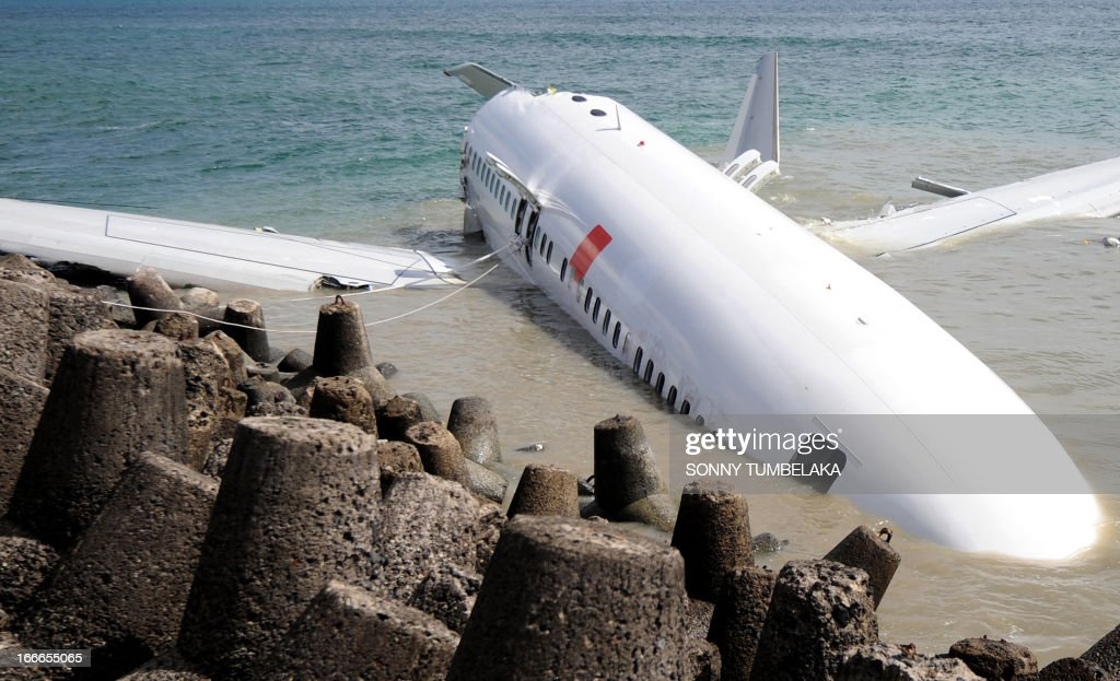 A Lion Air Boeing 737 lies partially submerged in the water two days after it crashed while trying to land at Bali's international airport near Denpasar on April 15, 2013. The pilot and co-pilot of a Lion Air plane that crashed at Bali's airport have passed initial drug tests, an official said on April 15, as investigators probe the causes of the accident that left dozens injured but no fatalities. AFP PHOTO / SONNY TUMBELAKA