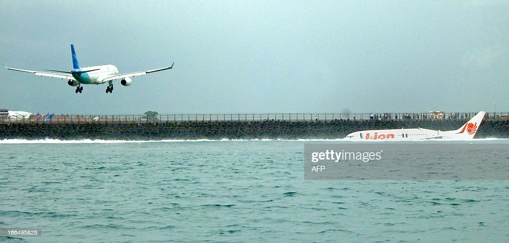 A Lion Air Boeing 737 (R) lies submerged in the water after skidding off the runaway during landing at Bali's international airport near Denpasar on April 13, 2013. An Indonesian plane carrying more than 100 passengers broke in two after missing the runway at Bali airport on April 13 and landing in the sea, leaving dozens injured but no fatalities. AFP PHOTO/Karna Surya Putra